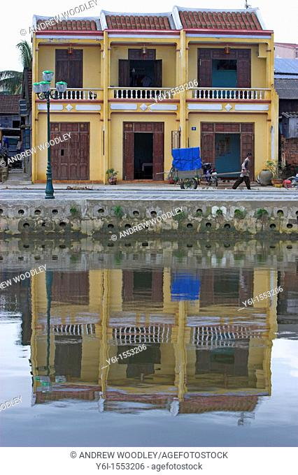 Man with hand cart and three pastel yellow terrace house reflected in river Hoi An historic town mid Vietnam