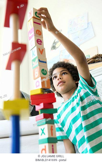 Mixed race boy building wooden block tower in living room