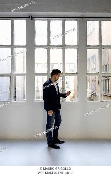 Businessman standing in a loft at the window using cell phone