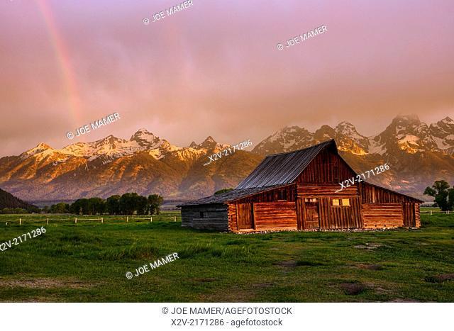 Moulton Barn at sunrise with rainbow on Mormon Row against the Teton Range Mountains in Grand Teton National Park