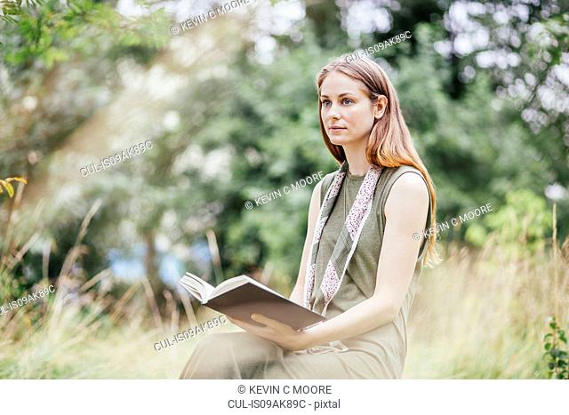 Young woman in field distracted from reading book