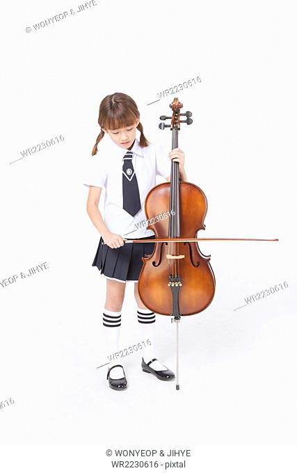 Elementary school girl in school uniform standing and playing the cello