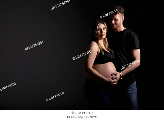 A young expectant couple with the mother looking at the camera while they are holding her belly in a studio on a black background: Edmonton, Alberta, Canada