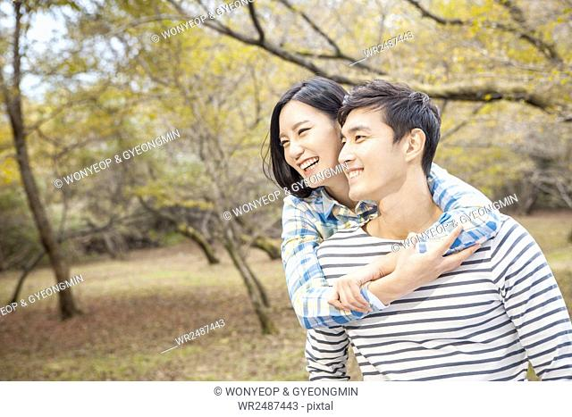 Side view portrait of young smiling couple in park