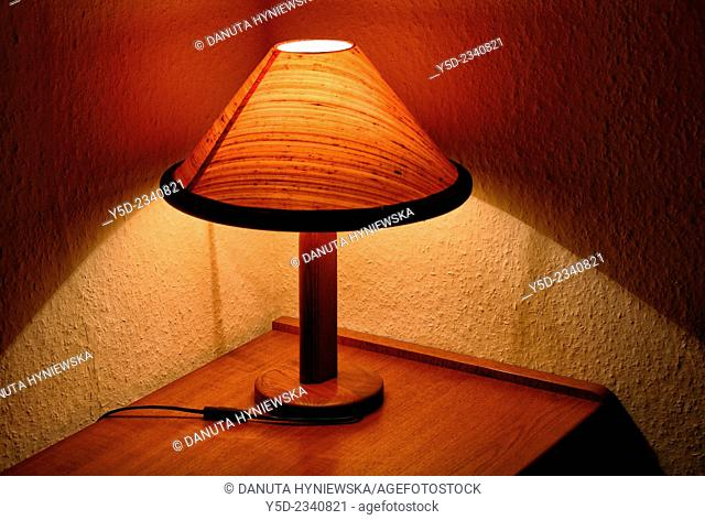 close-up of small lamp illuminating corner of room at night