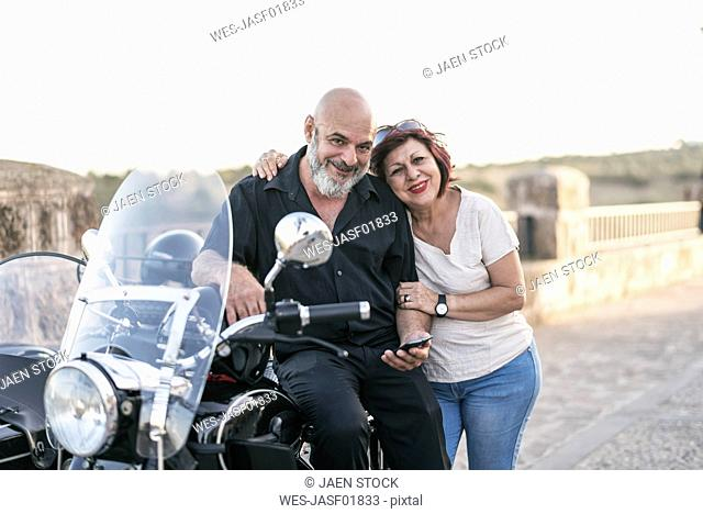 Spain, Jaen, portrait of mature couple with motorcycle with a sidecar