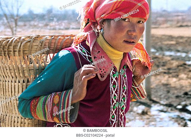 Portrait of a mid adult woman carrying a basket, Ninglang County, Lijiang City, Yunnan Province of People's Republic of China