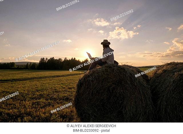 Mari man sitting on hay bale at sunset using laptop