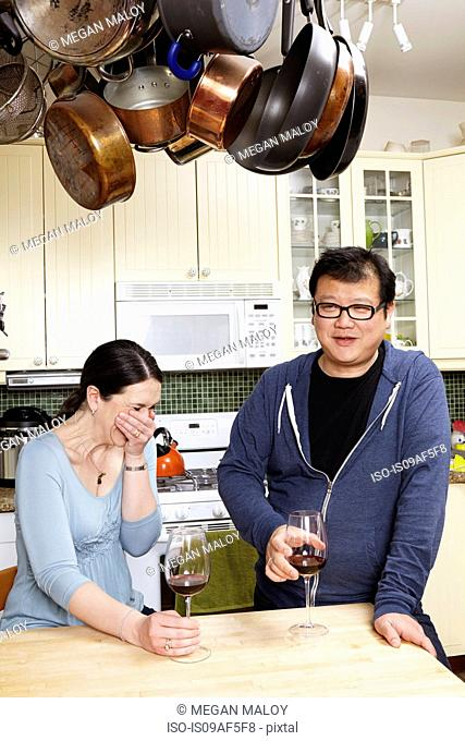 Mature couple relaxing with a glass of wine in kitchen
