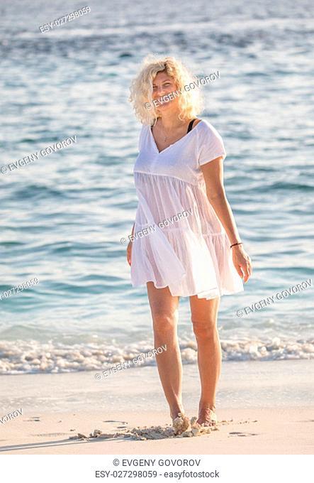 Beautiful woman is walking on the Maldivian beach
