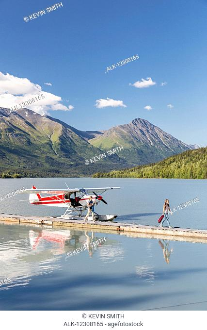 Two women disembark from a float plane docked at the Trail Lake Float Plane Base on a clear day, the Kenai Mountains in the Background, Kenai Peninsula