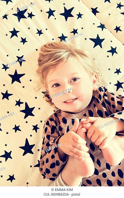 Portrait of female toddler lying on star pattern bed holding her bare feet