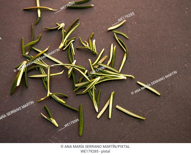 One rosemary blooming twig and rosemary leaves on a slate plate