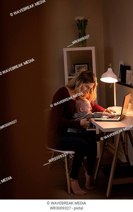 Mother using laptop while sitting with baby