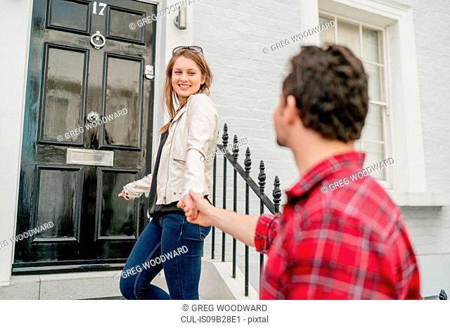 Young woman and boyfriend at front door, Kings Road, London, UK