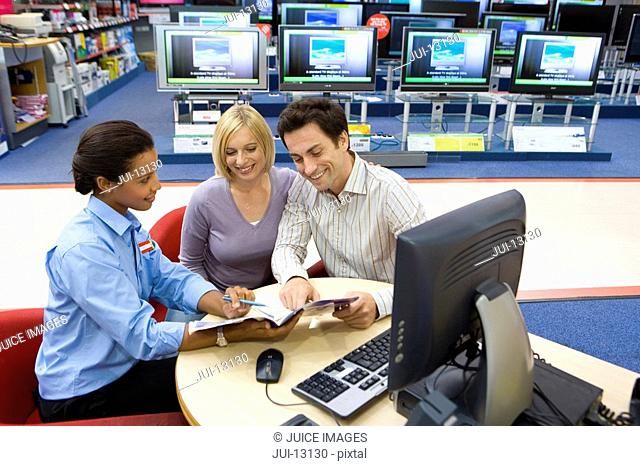 Saleswoman assisting young couple in electronics shop, smiling, elevated view