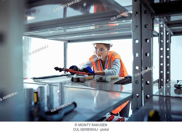 Female apprentice selecting tools at railway engineering facility
