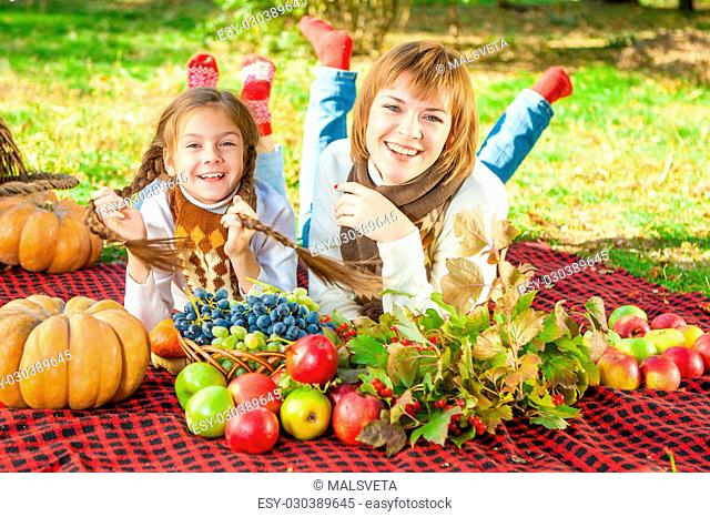 beautiful happy mother and daughter lying on a picnic. Autumn harvest. Apples, pumpkins, grapes, viburnum