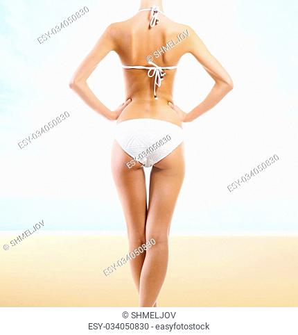 Beautiful body of young and sexy woman. Sea, sky, palms and beach background. Summer vocation concept