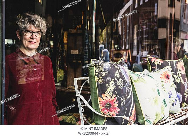 Smiling senior woman wearing glasses and red dress standing in interior design store, looking at camera