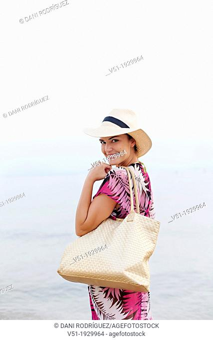 Woman with hat arriving at the beach smiling at camera