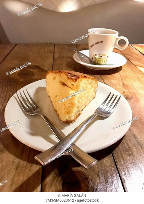 Sponge cake with two forks and cup of coffee in a cafe