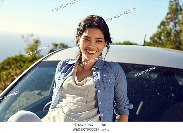 Smiling young woman at a car