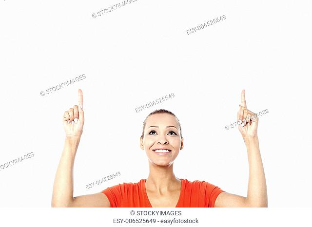 Attractive young woman pointing upwards