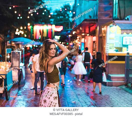 Thailand, Bangkok, young woman in the city on the street at night