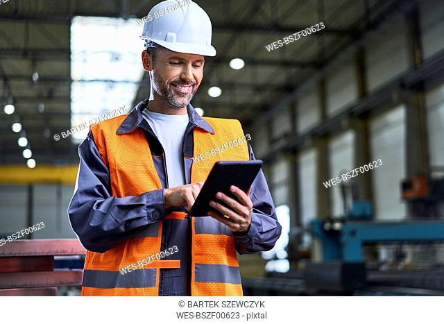 Smiling man using tablet in factory