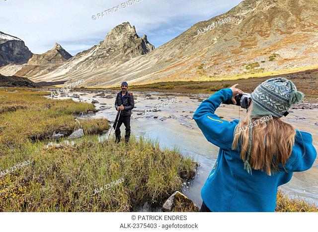 Hiker takes a picture in the Arrigetch Peaks, Arrigetch creek, Gates of the Arctic National Park, Alaska