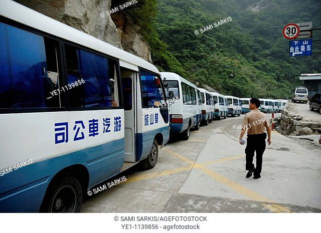 Man searching among a row of tourist buses parked on Mount Hua, one of China's five Sacred Taoist Mountains, in Shaanxi, China