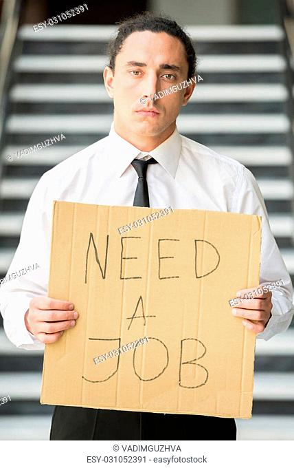 Man in suit holding sign in hands. Unemployed man looking for job