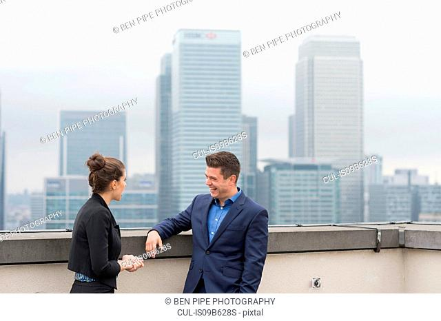 Businessman and female colleague meeting on city office roof terrace, London, UK