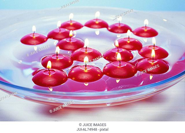 Detail view of tea candles floating in a bowl of water