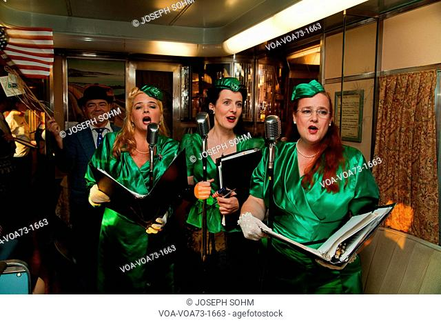1940's female reenactors sing on Pearl Harbor Day Troop train reenactment from Los Angeles Union Station to San Diego