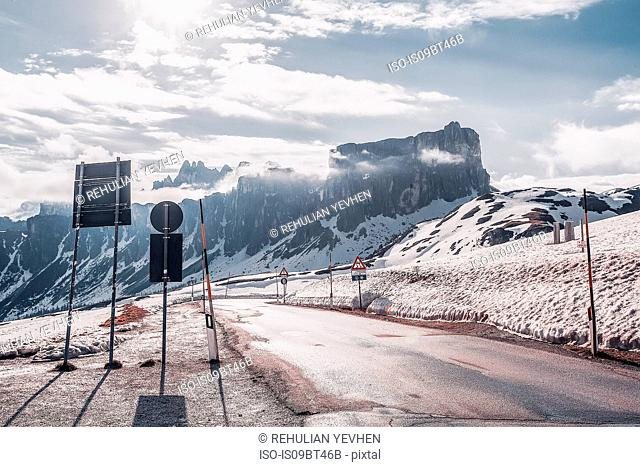 Rural road in snow capped mountains, Dolomites, Italy