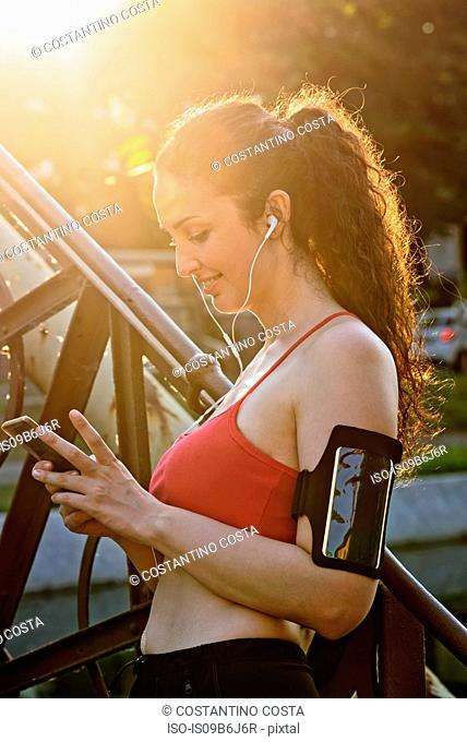 Young female runner wearing earphones and looking at smartphone in sunlight