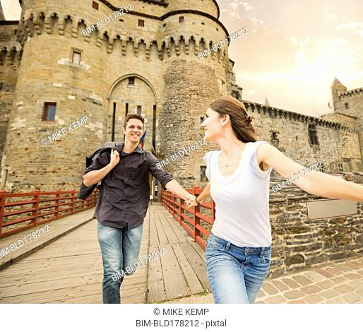 Caucasian couple running at castle