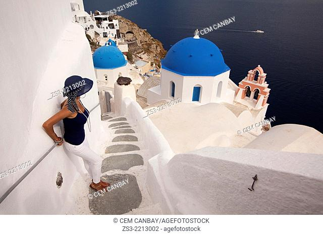 Woman in front of a blue domed church in Oia town with a ferry at the background, Santorini, Cyclades Islands, Greek Islands, Greece, Europe