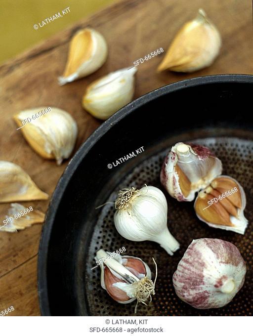 Various varieties of garlic in and beside pan