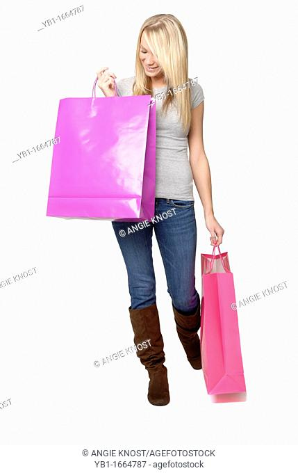 Attractive young woman standing with two shopping bags