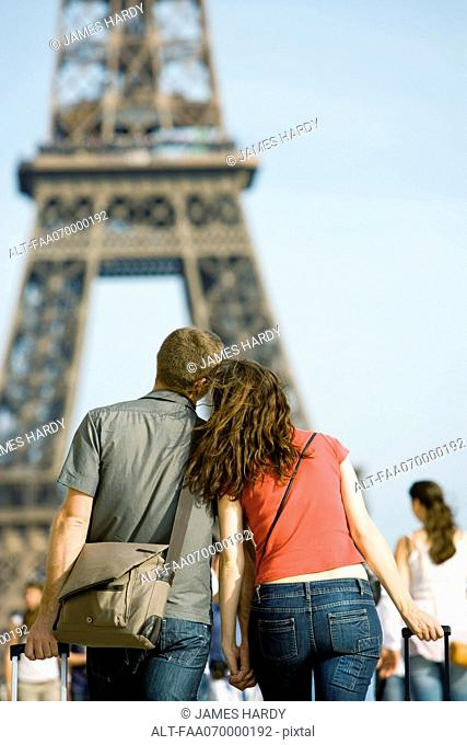 Tourist couple walking hand in hand toward Eiffel Tower, Paris, France