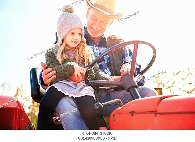 Farmer and granddaughter at pumpkin farm