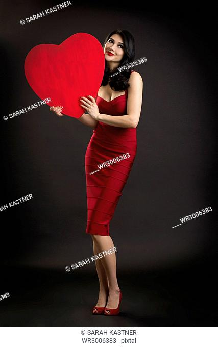Woman in red evening dress holds a heart