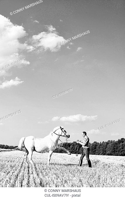 B&W image of man training white horse in field