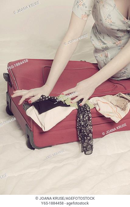 a woman tries to close a suitcase