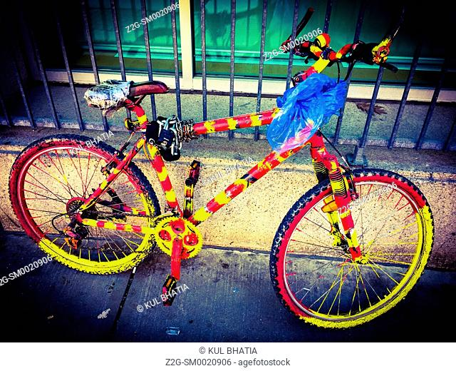 A bicycle in psychedelic Colors tethered to an iron fence, Ontario, Canada
