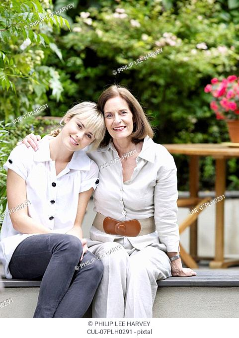 Mother and daughter sitting in garden
