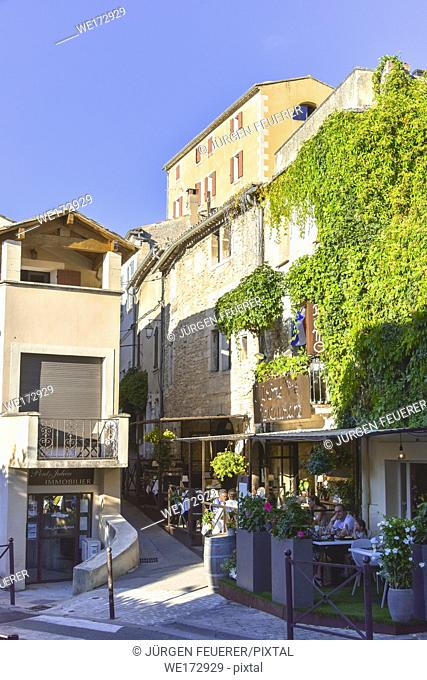stone buildings and picturesque lane with cafe in Bonnieux, Provence, France, massif of Luberon, region Provence-Alpes-Côte d'Azur